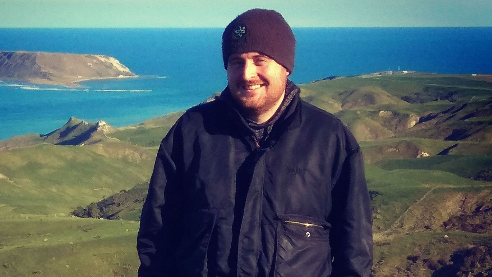 Harry, wearing a black jacket and beanie, stands in front of green hills and blue ocean. A small island can be seen in the distance.