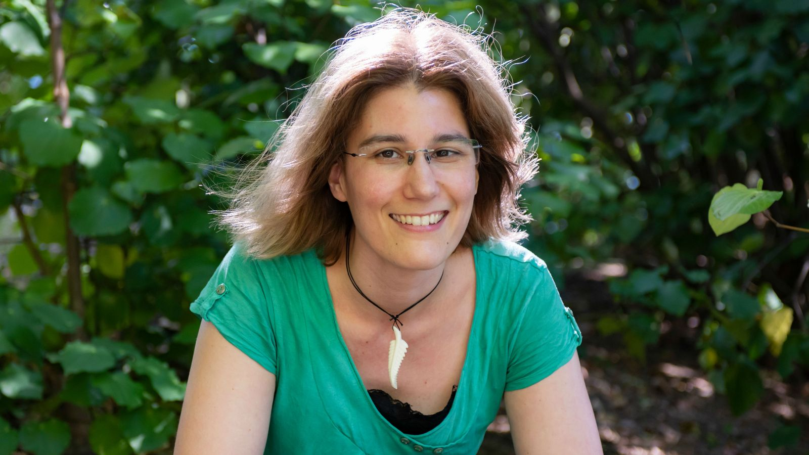 image of PhD candidate Geraldine Smieszhala in a green top standing infront of foliage on campus