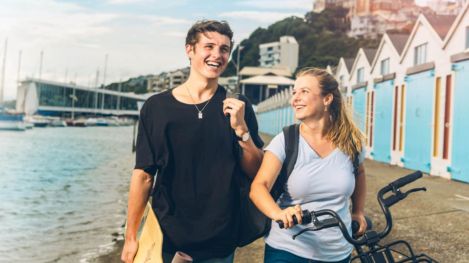 A male and female student are chatting and walking by the boatsheds at Oriental Bay, Wellington.