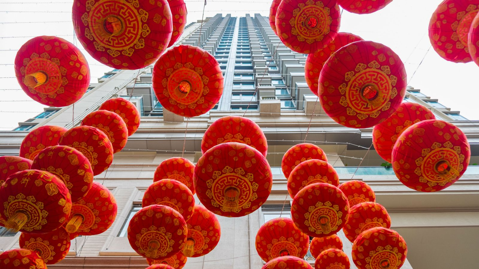 Red Chinese lanterns suspended overhead in front of a tall residential building.