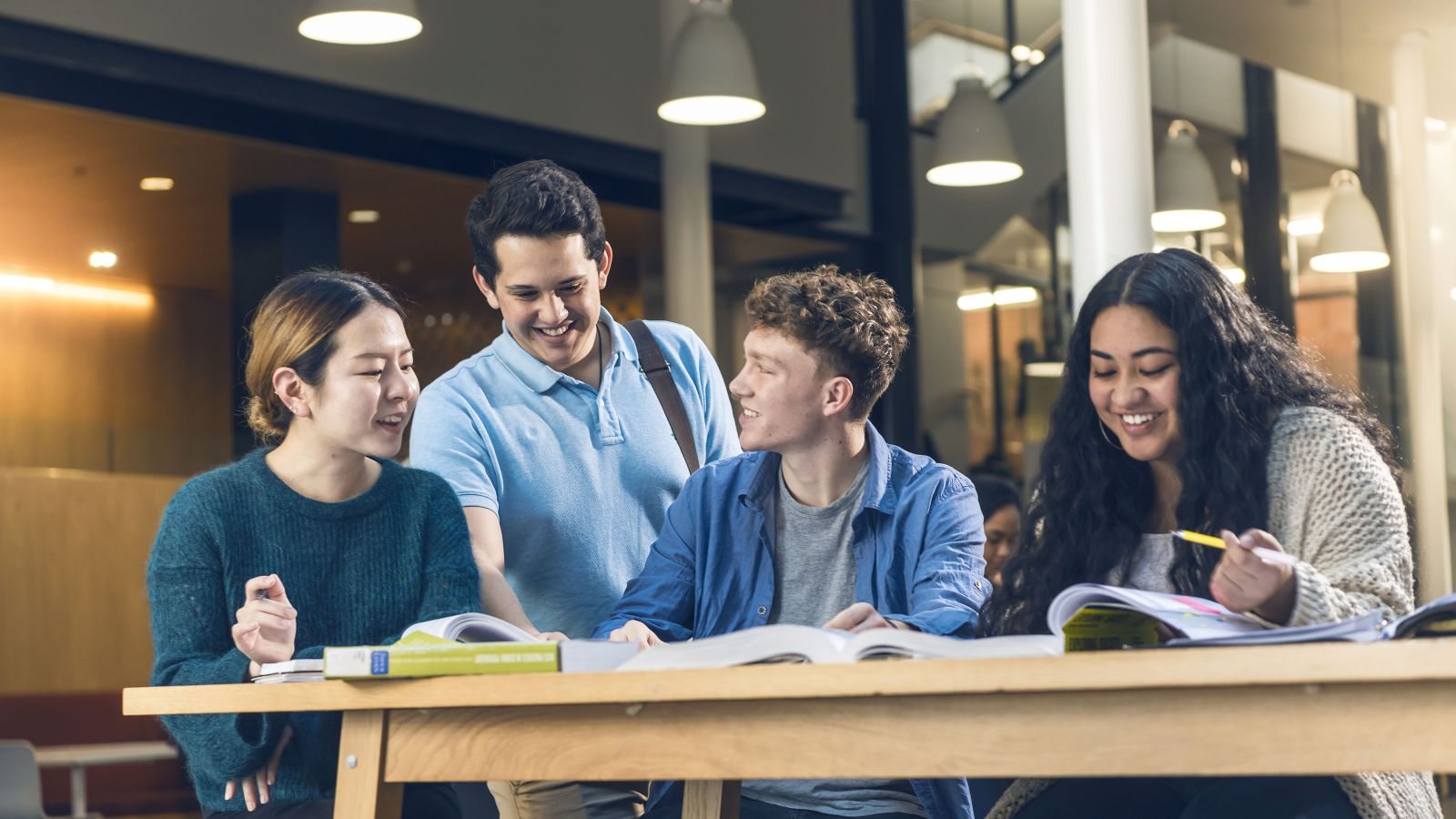 Four students, three sitting and one standing, study at a table with open text books on it.