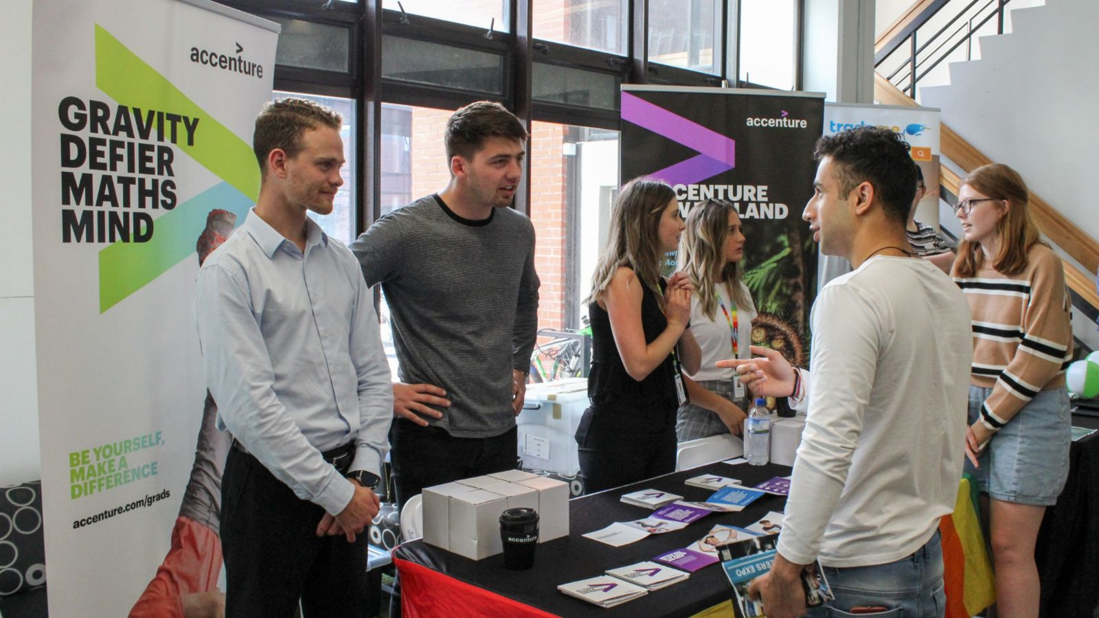 A male student engages with employers at an expo booth.