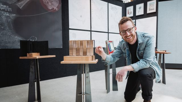 Patrick Kelly crouches with a wooden architectural model in front of an exhibition of architectural models and maps
