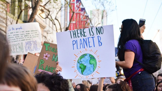 A group holding a poster that reads, there is no planet b.