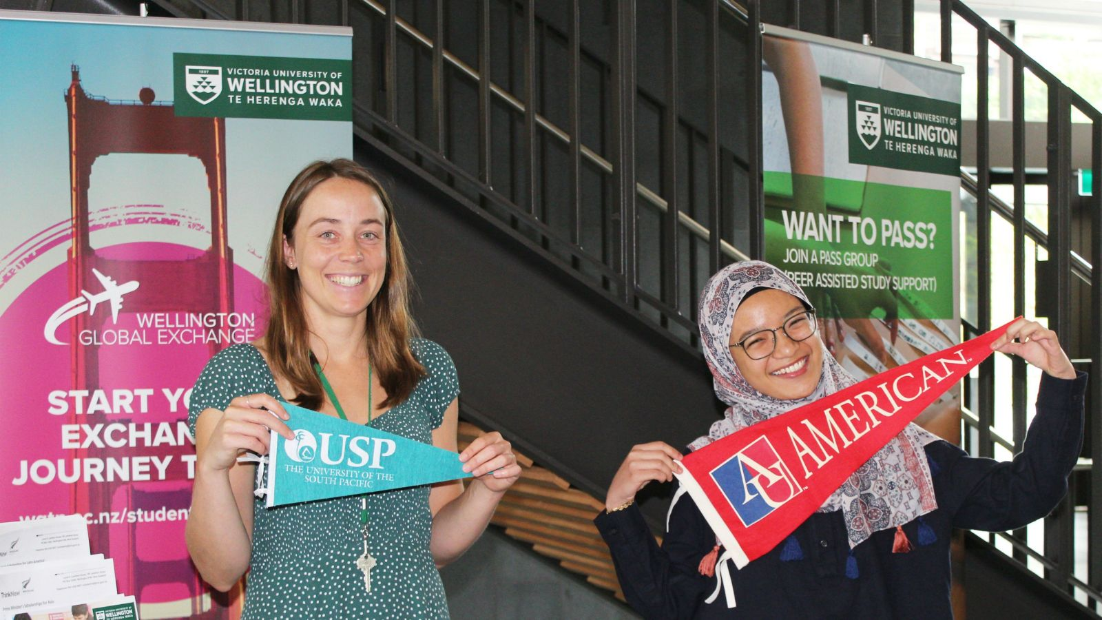 Staff member Grace Patterson and student holding pennants of exchange partner universities at the exchange booth during the International Student Orientation Expo in Trimester 1, 2020.