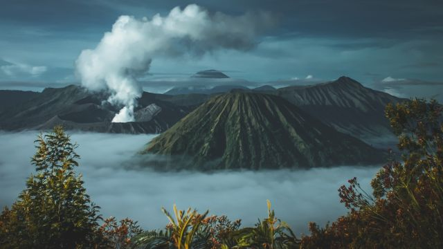 An image of steep mountains and a steaming volcano.