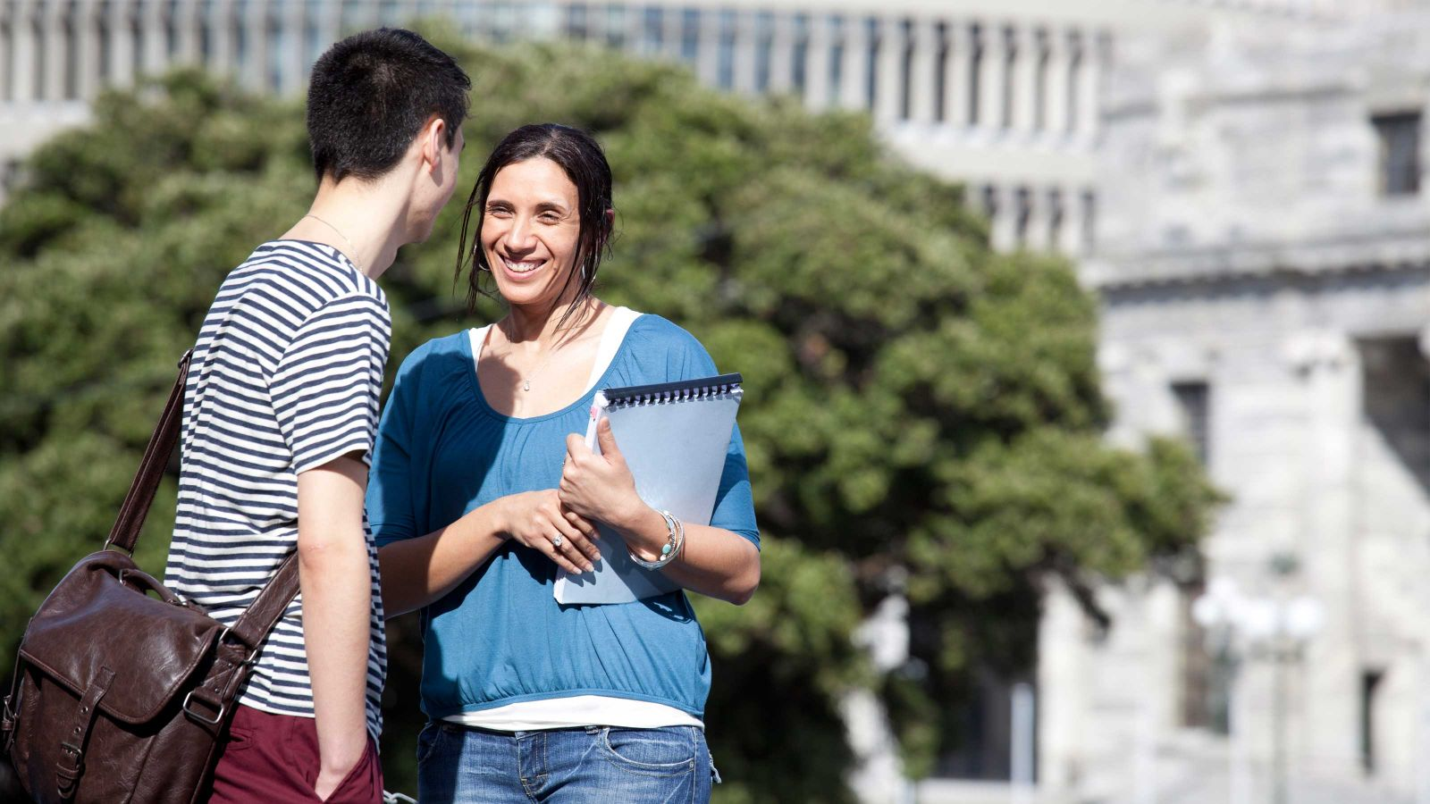 Future Maori students enjoying a conversation outside on a sunny day with grey stone buildings in the background.
