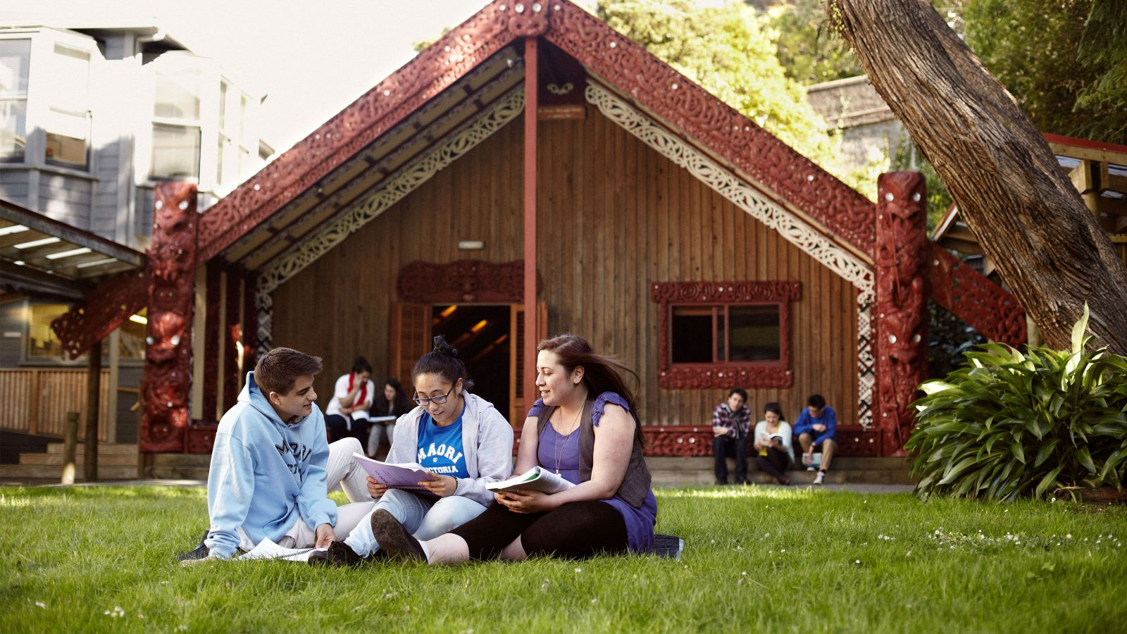 Students sit in front of the Marae.