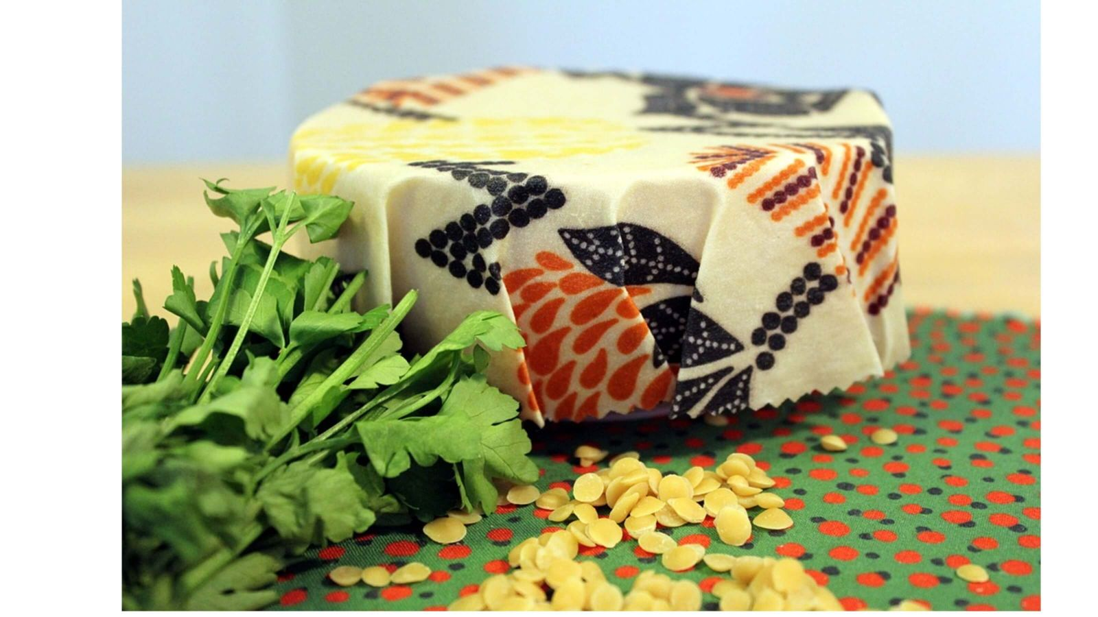 Bees wax wraps – container covered in beeswax wrap, celery and beeswax pellets.