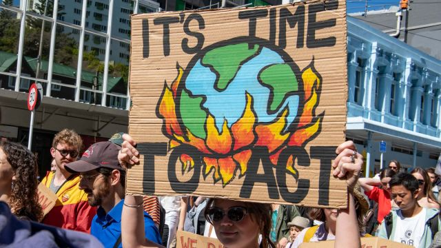 Woman holding sign saying 'It's time to act' at Climate March in Wellington CBD