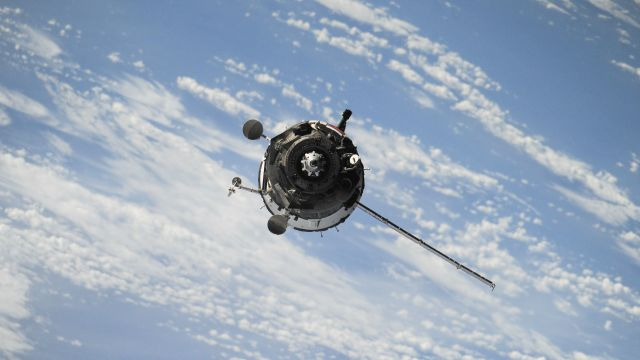 A satellite flying in front of clouds and blue sky.