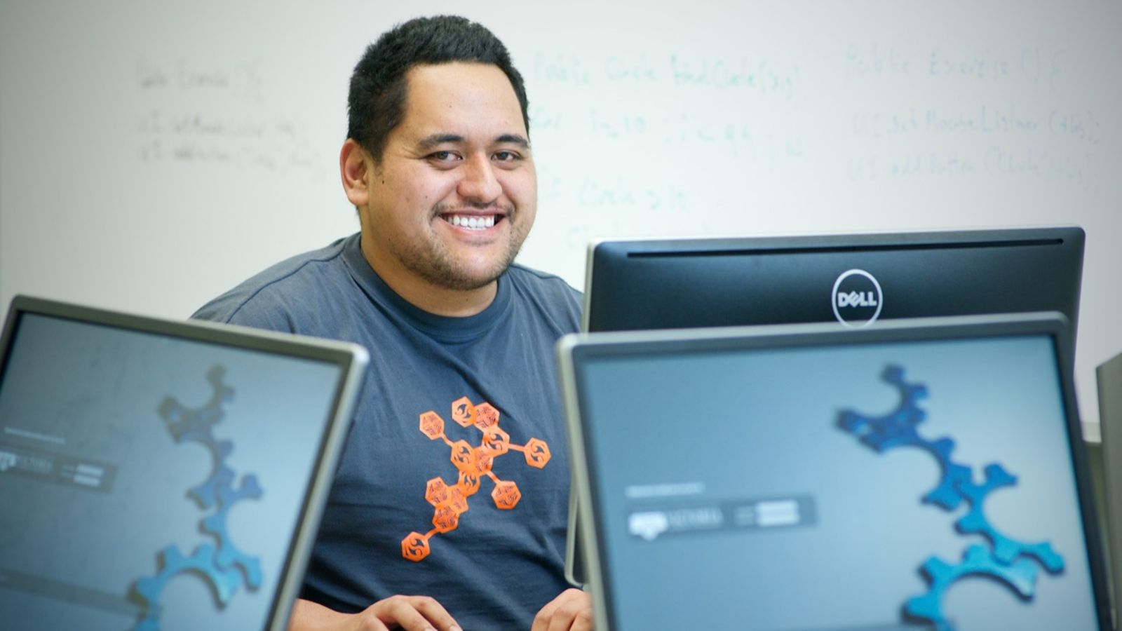 Photo of engineeirng student Michael Tololi surrounded by computer monitors.