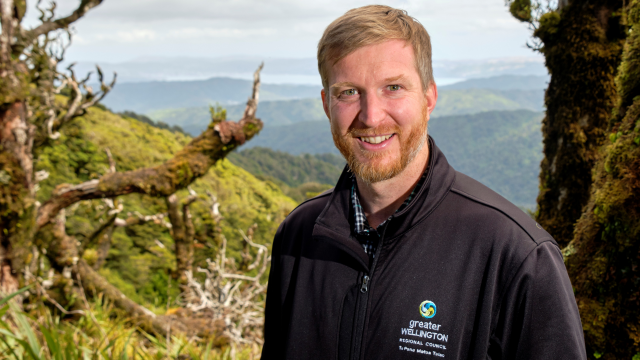 Red haired man with beard and moustache against natural backdrop with trees