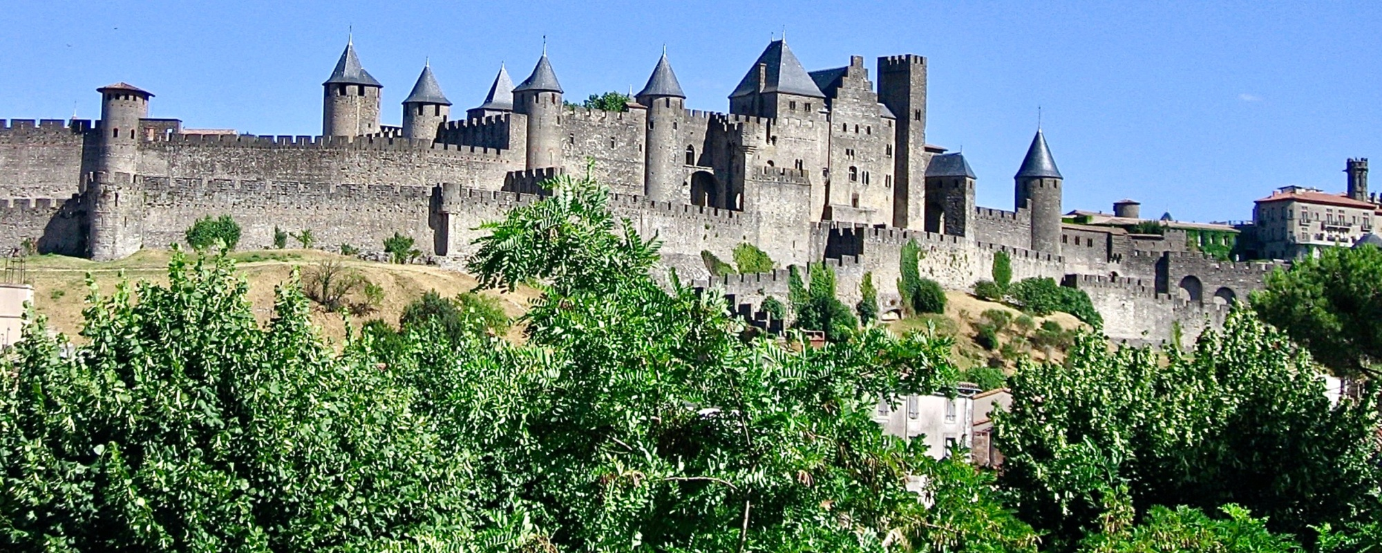 Wide view of exterior of grey medieval castle with crenellated walls and several turrets.