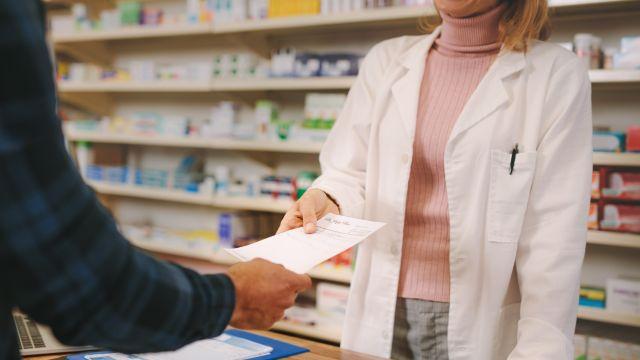 A pharmacist serving a customer