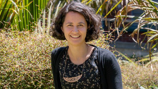 Dr Awanui Te Huia photographed outside with a background of native New Zealand plants.