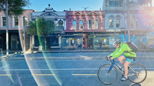person on bike with newtown buildings in background