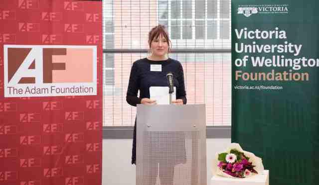 Annaleese stands behind a podium giving an speech.