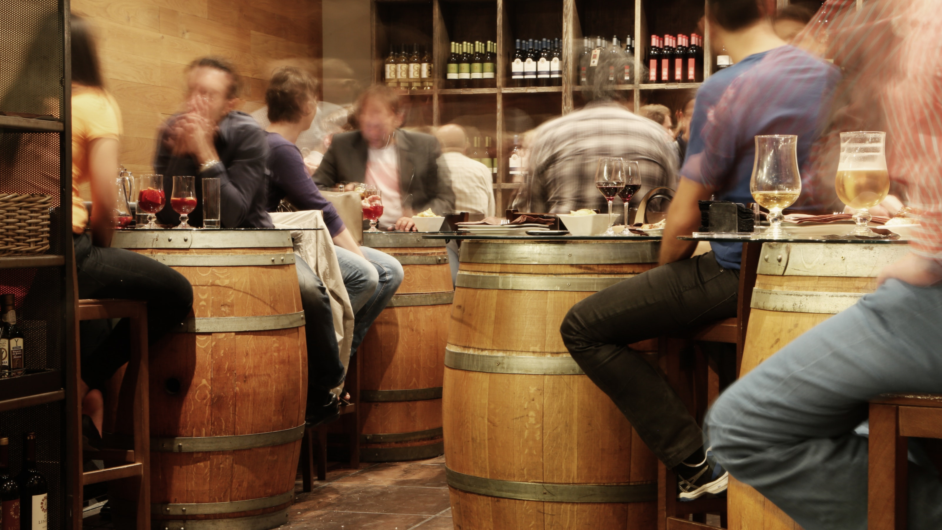 A rustic bar with barrel tables, drinks on them and people chatting.