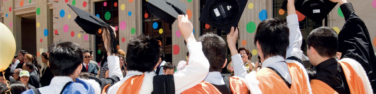 Banner image – students hold up their hats at graduation.