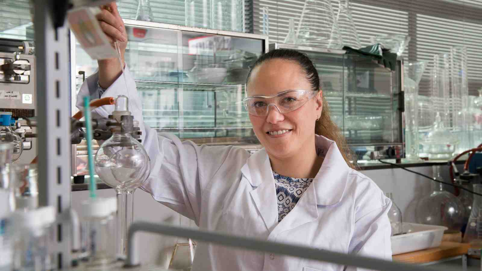 PhD Candidate Helen Woolner uses chemistry equipment in a laboratory.