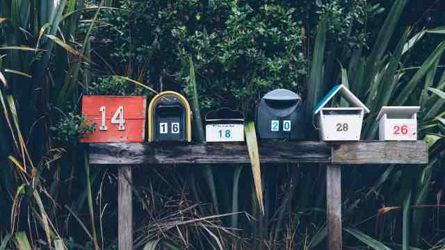 A collection of New Zealand postboxes surrounded by flax.