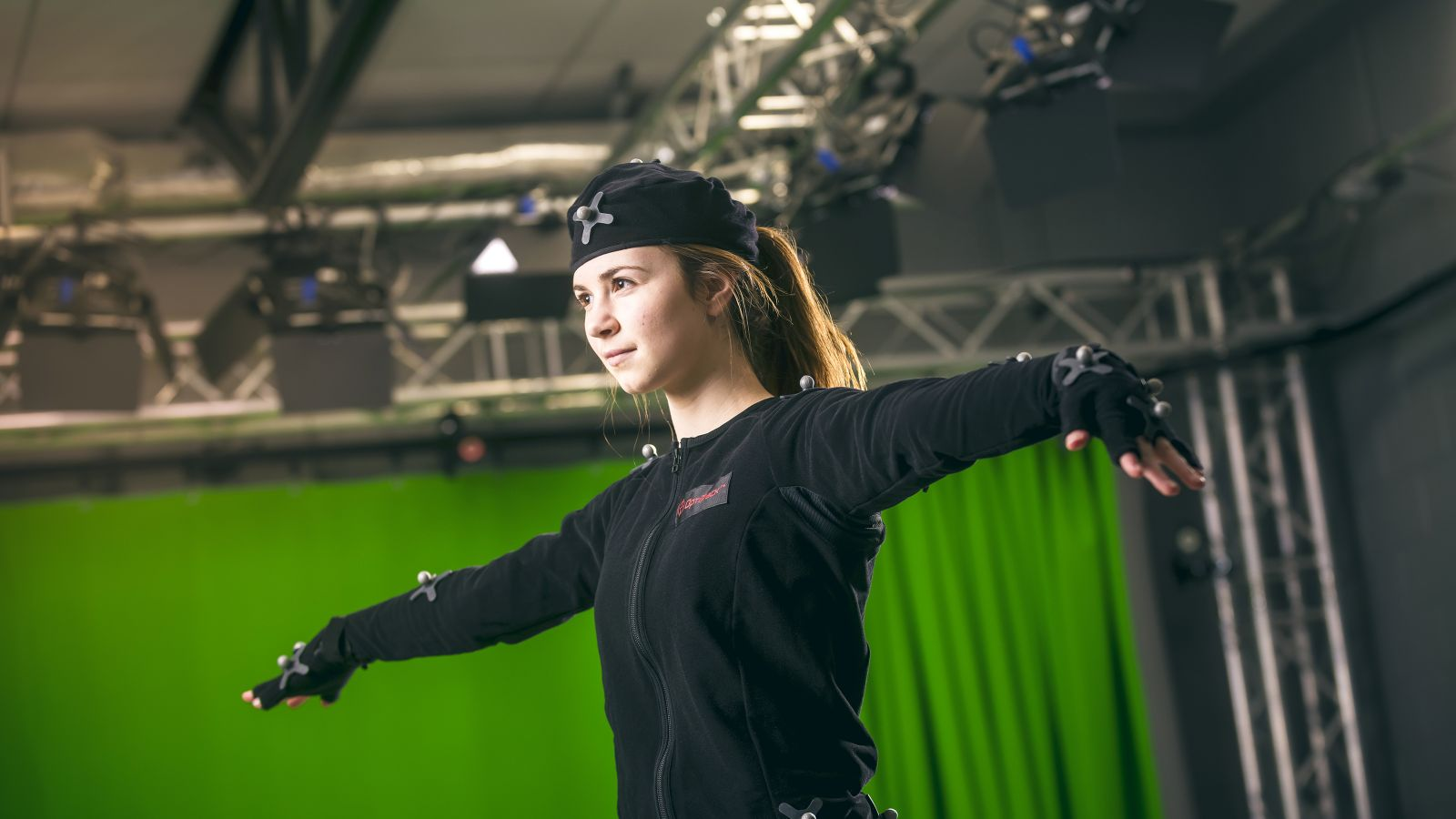 A female student in a motion capture student extends her arms in front of a green screen.