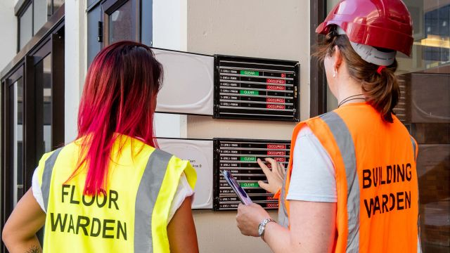 Two women looking at an evacuation board. One woman wears a yellow vest labelled floor warden and the other woman wears an orange vest labelled building warden.