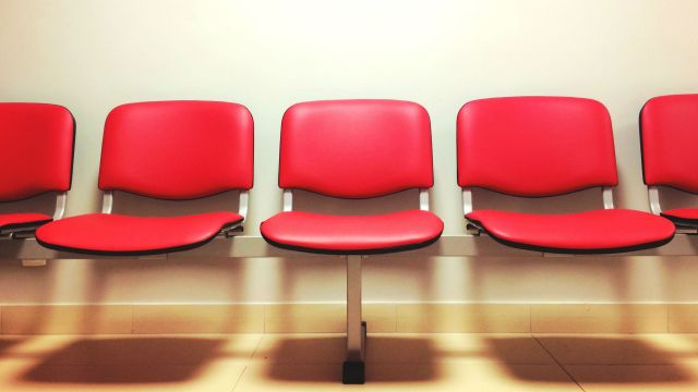 Red chairs in a doctor's waiting room.