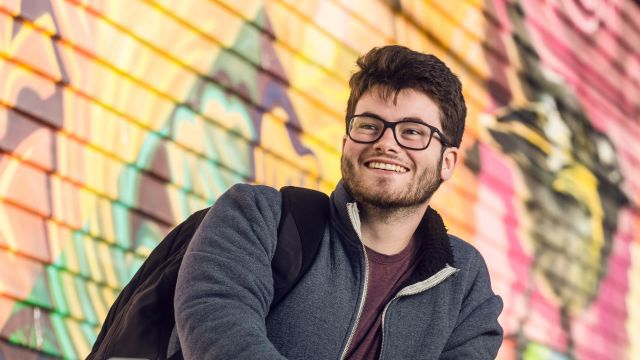 Smiling Education student, Michael, is standing with his backpack over one shoulder with a colourful mural behind him.