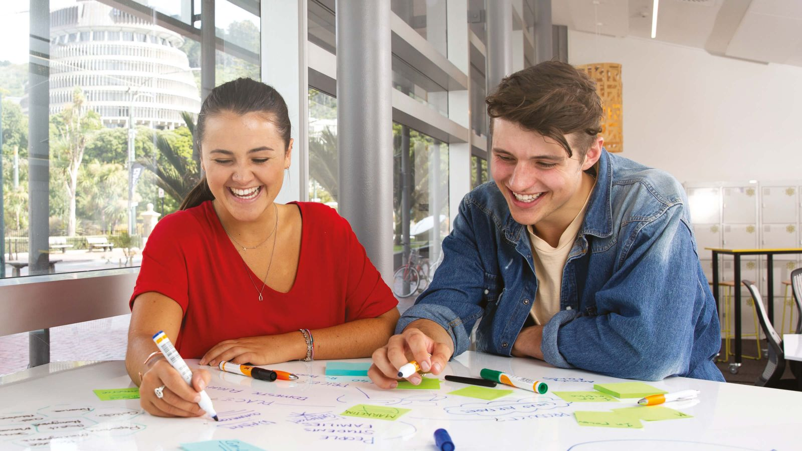 Two students sitting together and writing on a white board in a seminar room at the university's Pipitea campus.