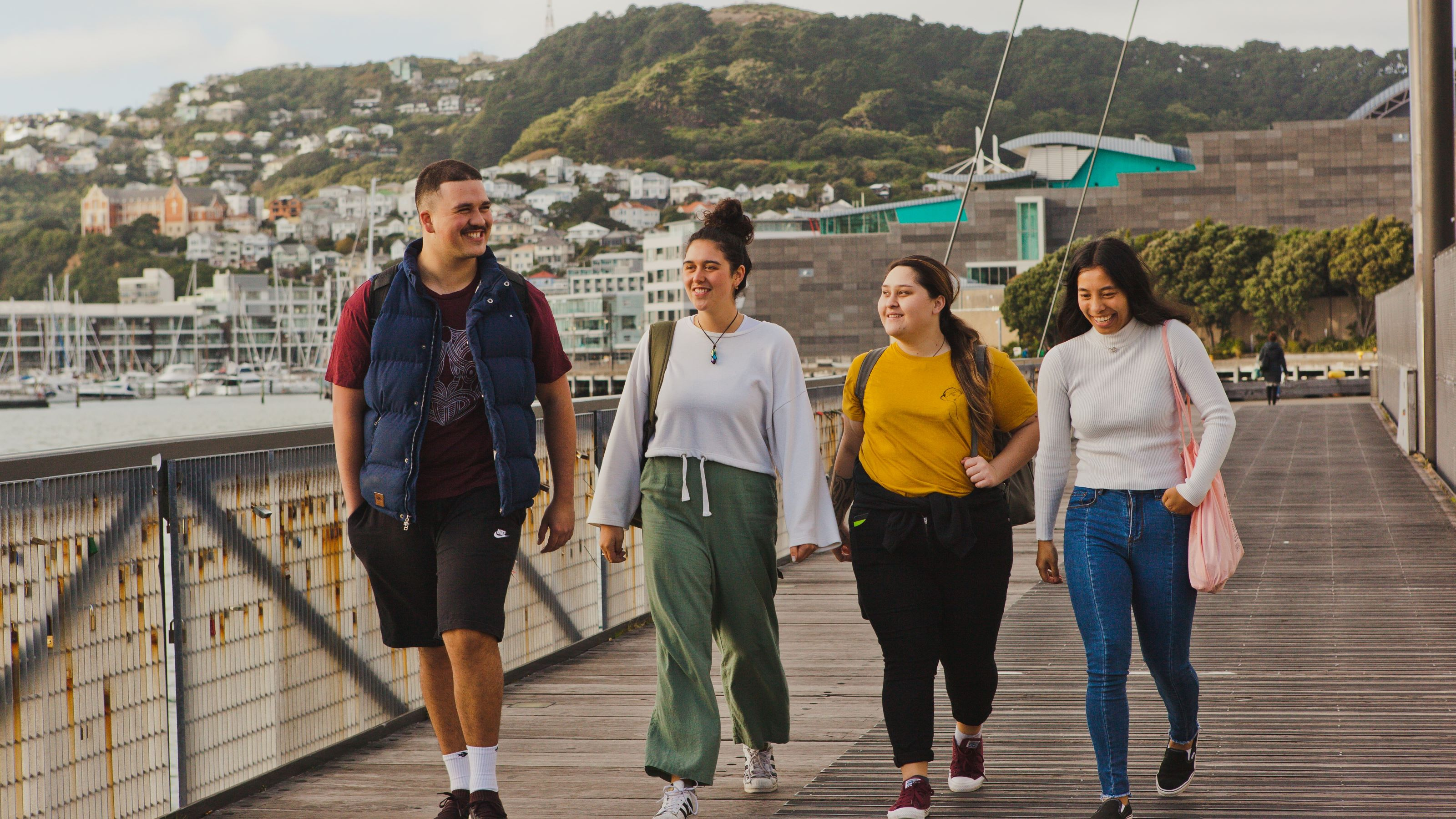 A group of 4 students walk along the Wellington waterfront