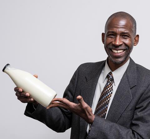 Professor Ian Williamson holding a glass milk bottle