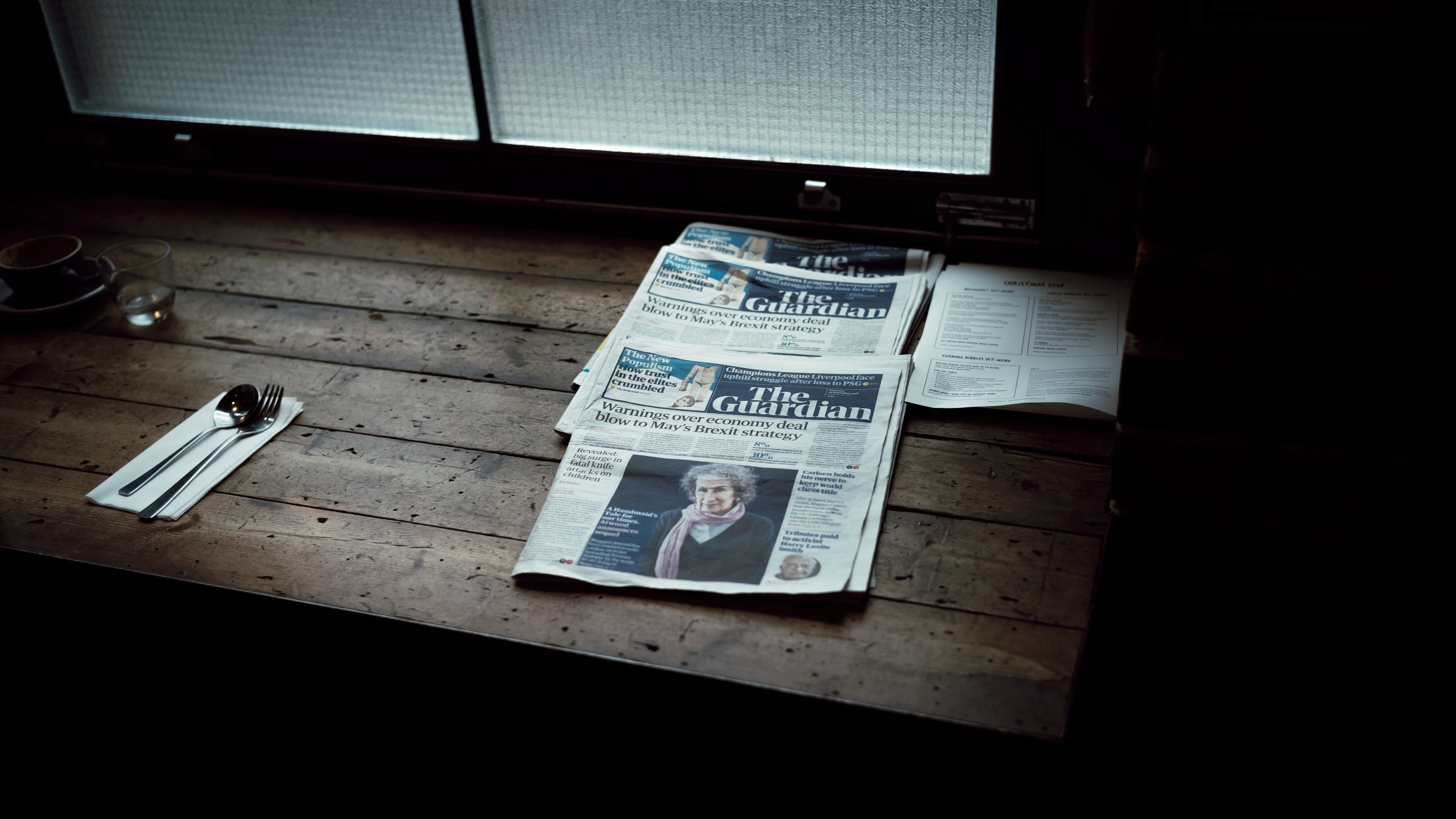 print issues of the guardian lying on a table