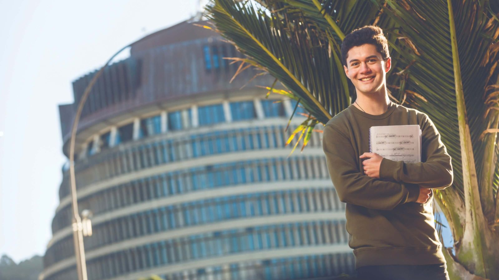 Smiling student, Reuben, is standing holding a book in front of the Beehive in Wellington.