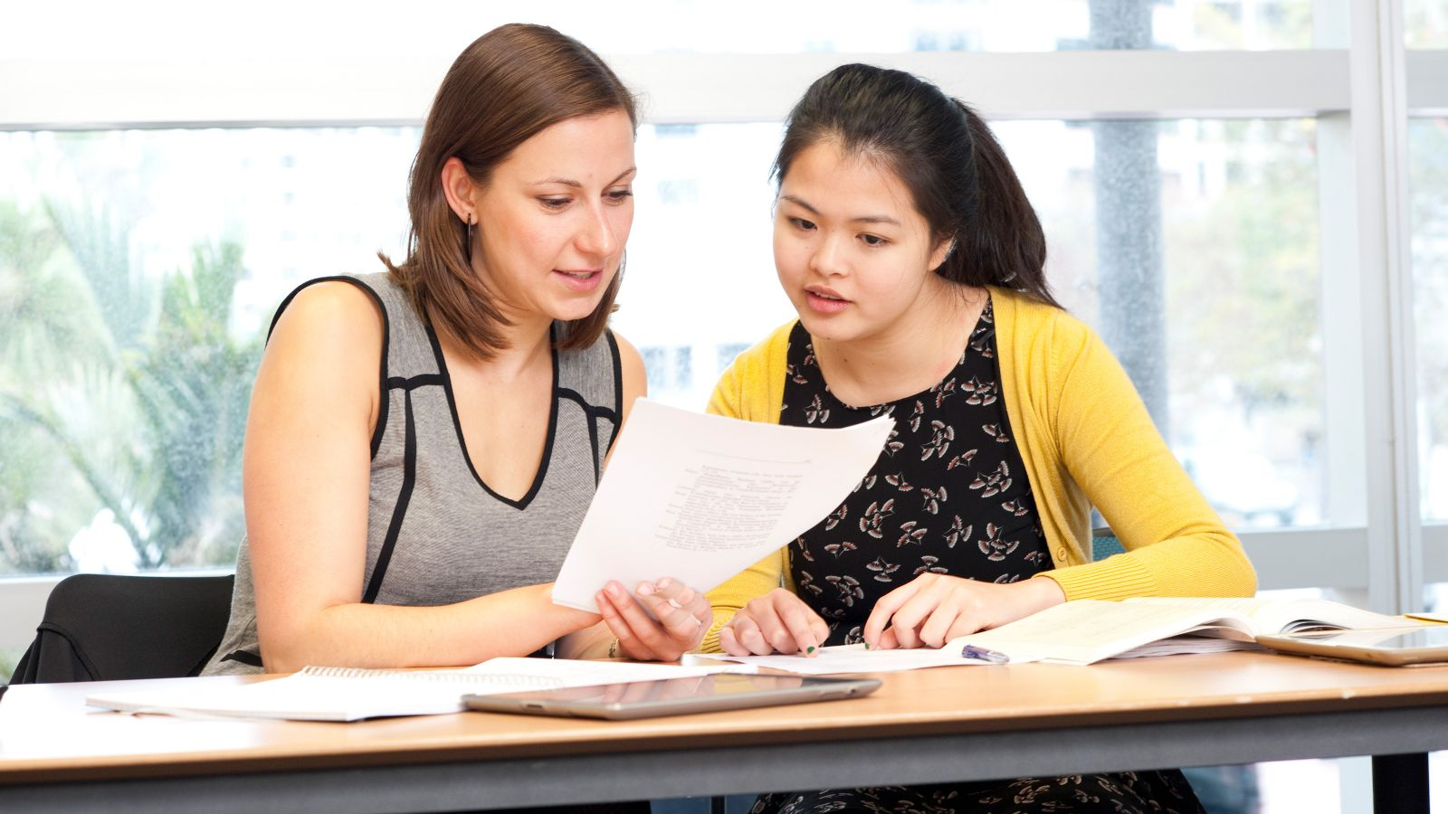 A lecturer and student reviewing a piece of work together