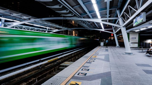 Modern train station with blurred train passing at full speed.