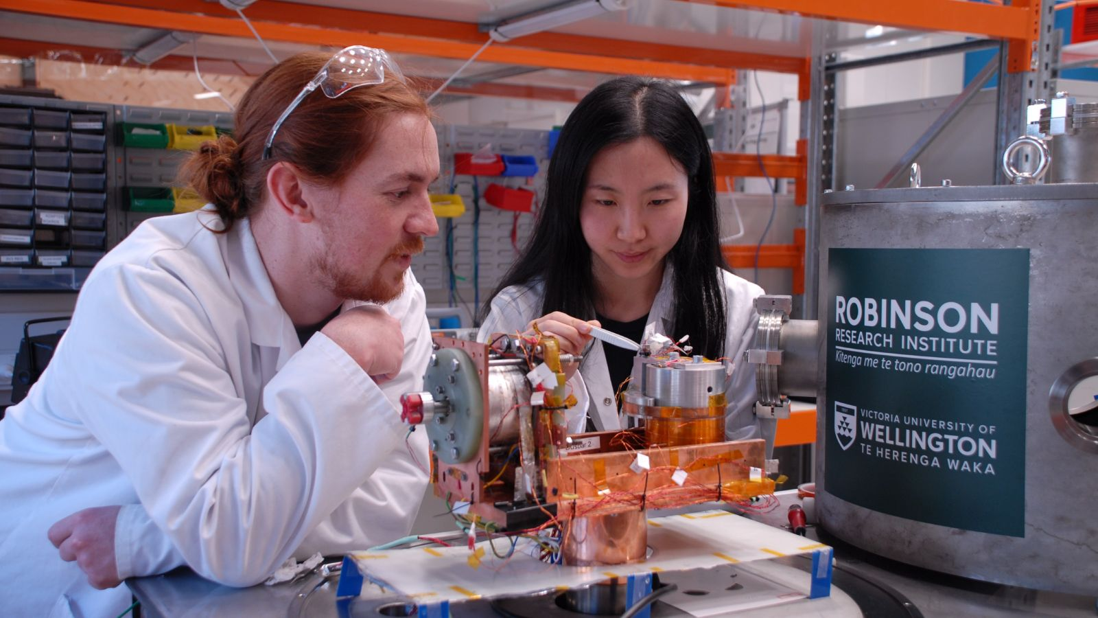 Two students in lab coats, working together on an electric system in Robinson Research Institute/
