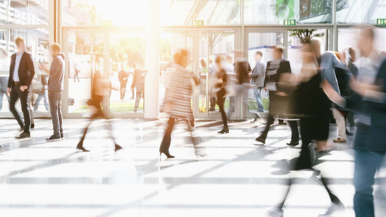 Abstract image of people walking through a busy foyer