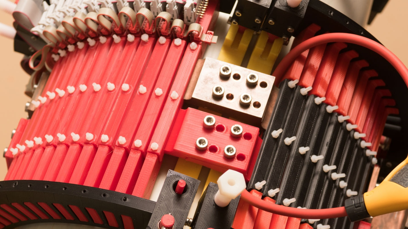 A cylindrical device with many red polymer slats and electronic cables.