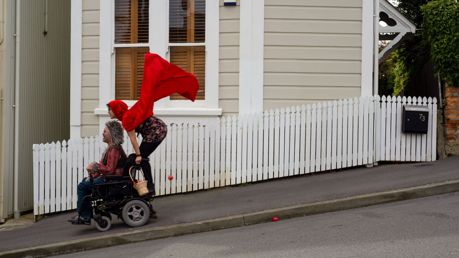 A man dressed as a wolf drives a motorised wheelchair down a steep street with a woman dressed like Little Red Riding Hood with a red cape and basket stands on the back.