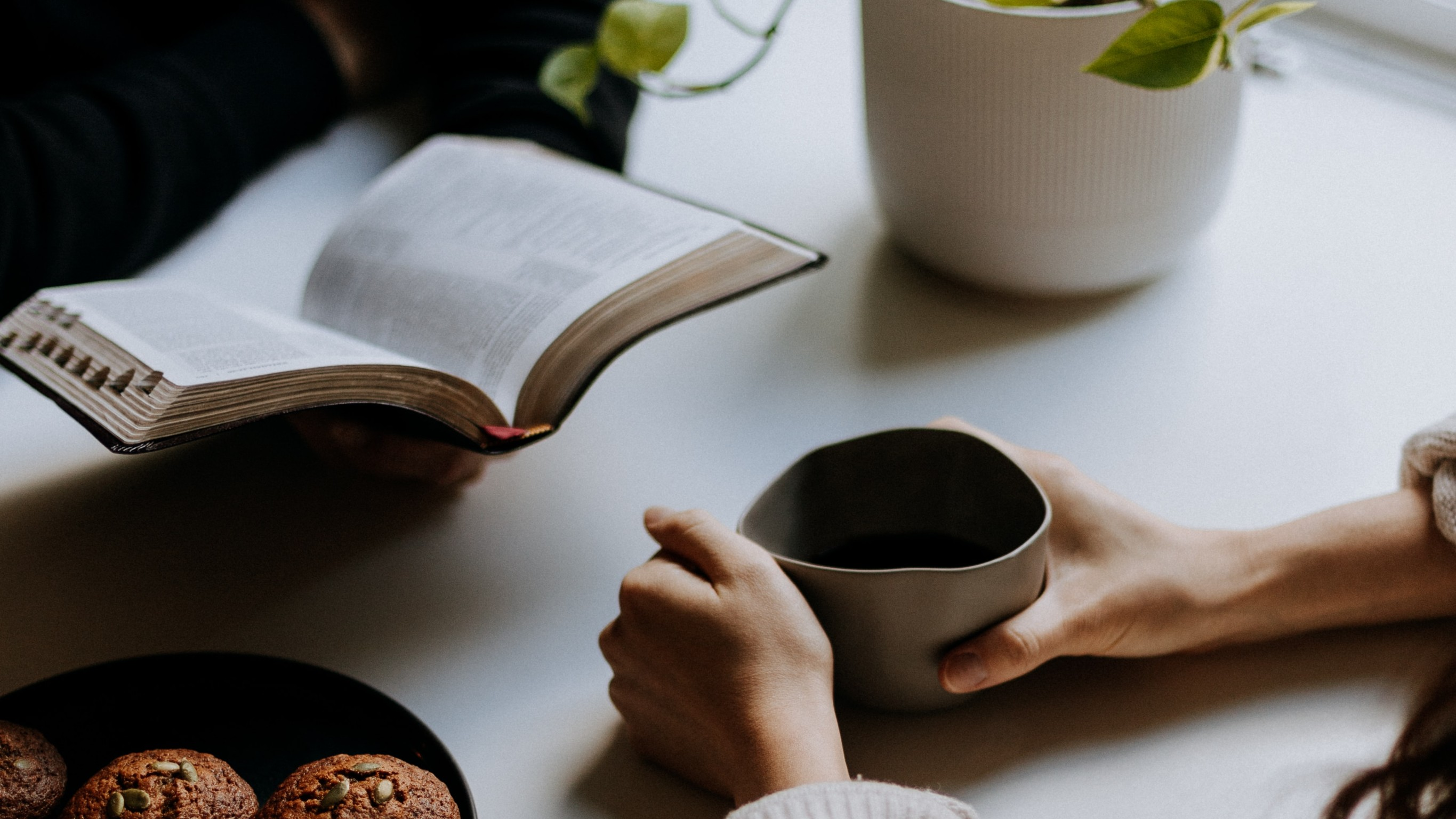 Table with woman's hands holding tea cup and another person holding a religious book.