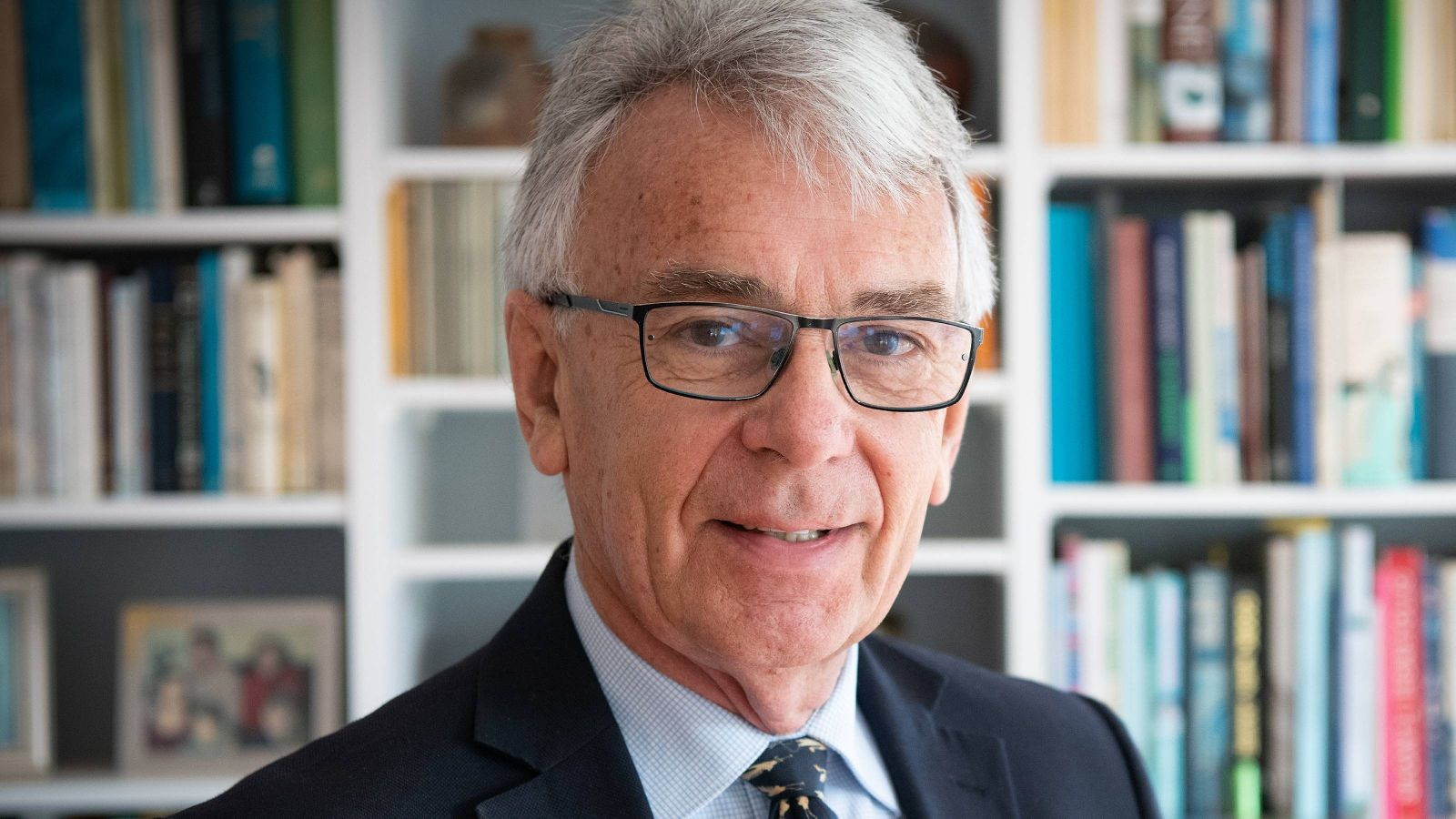 Portrait photo of distinguished alumnus Maarten Wevers in front of a bookcase.
