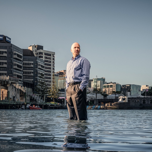Man standing knee-deep in water, with city landscape in the background.