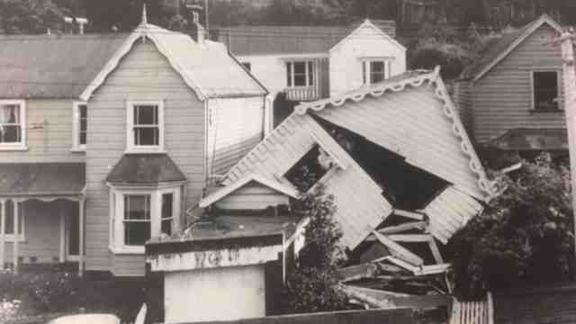 A black and white image of houses in a street, the house on the right has collapsed.