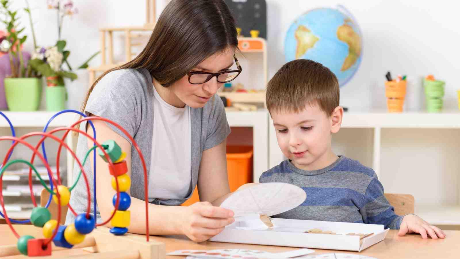 School teacher with child investigating puzzles