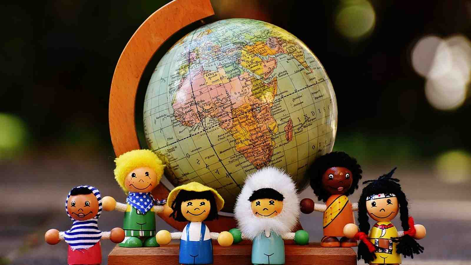 Figurines from around the world standing in front of a globe.