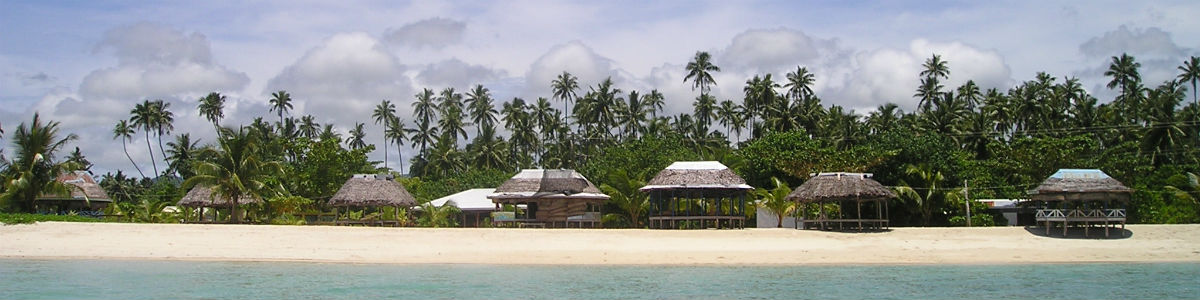 Banner image – several open-air huts built on a beach.