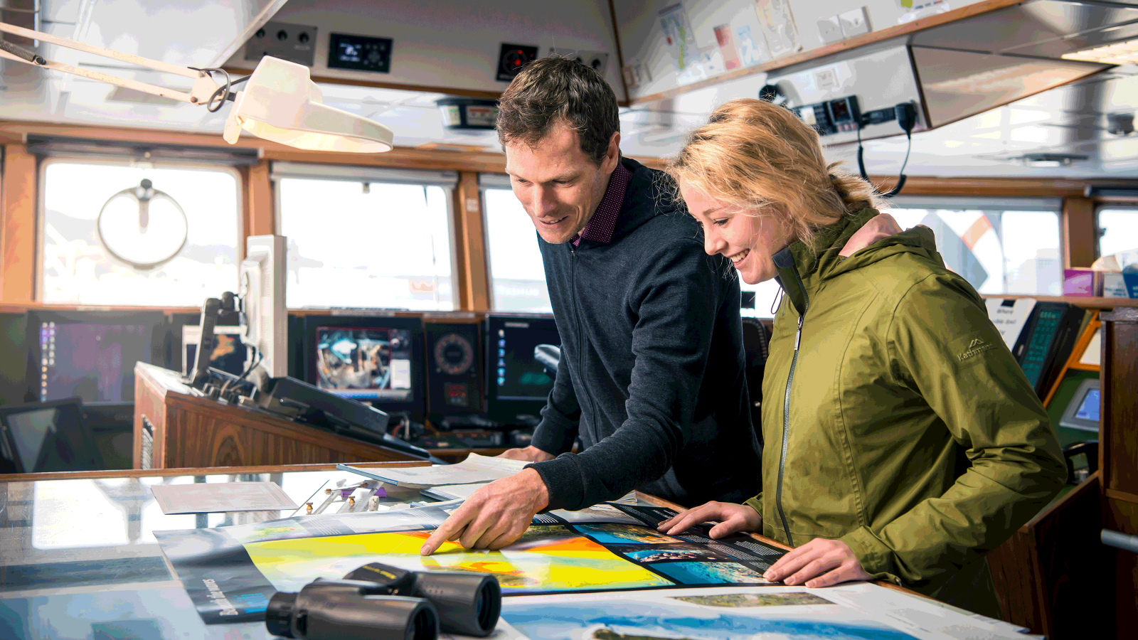 Two researchers look at a chart while standing in the control room of a ship.