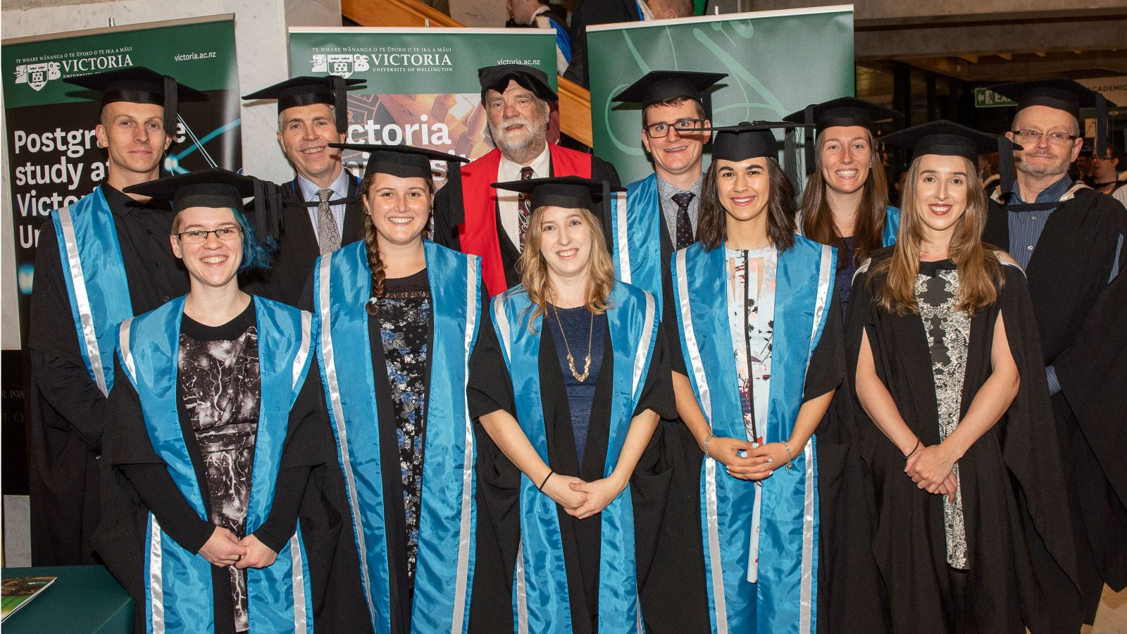 The eight Meteorology graduates in two rows with the programme director and advisors from MetService. They all wear graduation caps and gowns and there are Victoria banners behind them.